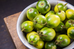 Some green tomatoes. In dish on wooden background Stock Photo