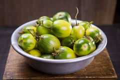 Some green tomatoes. In dish on wooden background Stock Images