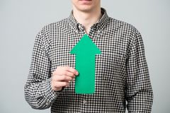Young man with green arrow Stock Image
