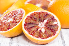 Some halved Blood Oranges. (close-up shot) on wooden background stock photography