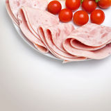 Some ham slices on plate with tomatoes.  Stock Photo