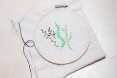 Some hand embroidered green plants. Hand embroidery in a frame with a needle by the side Stock Photo