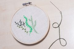 Some hand embroidered green plants. Hand embroidery in a frame with a needle by the side Stock Photography