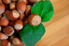 Some hazelnuts with leaves. Over wooden background Stock Photo