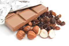 Some hazelnuts, raisins and chocolate bar. Chocolate, hazelnuts and raisins closeup on white background stock image