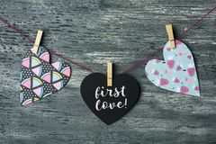 Hearts and text first love. Some hearts hung with clothespins in a clothes line and a black heart-shaped signboard with the text first love written in it royalty free stock image