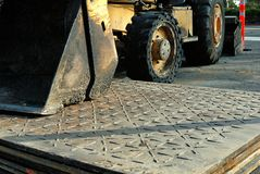 Steel plates used in road construction with a bull dozer in the background. Some heavy duty machinery is necessary to move some very heavy steel plates used to royalty free stock images