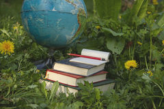 Some homework, daydreaming in the garden. Earth globe, pile of books, notes pad and pencil on the green grass stock photo