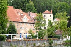 Some houses on the bank of Lech in the town of Landsberg am Lech in Bavaria (Germany). Photo made in the town of Landsberg am Lech in Bavaria (Germany). In the stock images