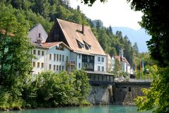 Some houses and a church beyond the river in the town of Fussen in Bavaria (Germany). Photo made in the town of Fussen in Bavaria (Germany). In the image, a stock image
