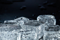 Some ice cubes. On black and wet surface stock images