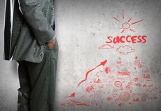 Some ideas for success. Bottom view of businessman and sketches of ideas on wall royalty free stock photo