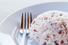 Some images of rice with fork in white dish. On brown wood table stock photo