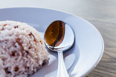 Some images of rice with spoon in white dish. On brown wood table royalty free stock photos