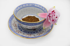 Some instant coffee. In an empty Cup with gold kaemochkoy on a saucer with fuchsia flower pink color Stock Photography