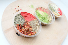 Some jars with colorful herbs and spices. Three jars with a mix of oriental spices on a light background. The focus of one jar, the rest are blurred. Is Royalty Free Stock Photos