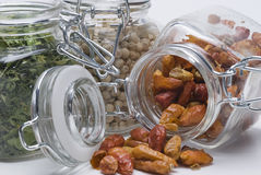 Some jars full of spices. Some glass jars with spices on a white background stock photography