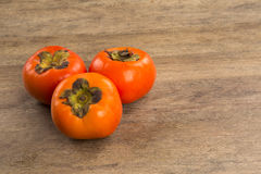 Some khaki fruits over a wooden surface Royalty Free Stock Photo