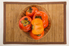 Some khaki fruits over a wooden surface Stock Photo