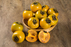 Some khaki fruits over a wooden surface Stock Image