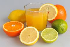 Some kind of citrus with the glass filled with citrus juice on t. He gray Stock Image
