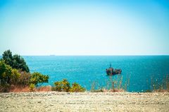 Some kind of merchant ship is at anchor near the shore of the Black sea. The ship is well visible from the height of the picturesque cliff Stock Images