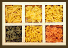 Some kinds of pasta and farfalle. In wooden tray Stock Photos