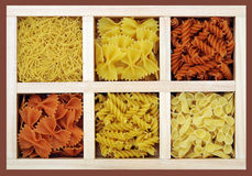 Some kinds of pasta and farfalle. In wooden tray Stock Photo