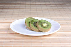 Some kiwi on the plate. Some kiwi pieces on the white saucer royalty free stock photography