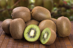 Some kiwis in a basket over a wooden surface. Fresh fruits royalty free stock photos