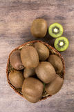 Some kiwis in a basket over a wooden surface. Fresh fruits royalty free stock image