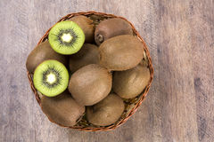 Some kiwis in a basket over a wooden surface. Fresh fruits Stock Images