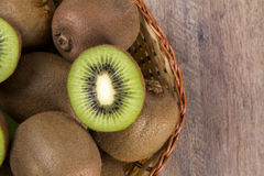 Some kiwis in a basket over a wooden surface. Fresh fruits royalty free stock photography