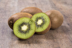 Some kiwis in a basket over a wooden surface. Fresh fruits stock photos