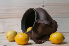 Some lemons and an old copper amphora. Still life with lemons and old copper amphora Royalty Free Stock Images