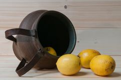 Some lemons and an old copper amphora. Still life with lemons and old copper amphora Royalty Free Stock Image