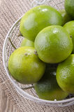 Some lime in a small basket. Some lime in a grey basket on jute Stock Image