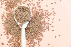 Some linseeds spread out on pink background seen from above. wooden spoon. Close up Royalty Free Stock Photography