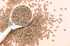 Some linseeds spread out on pink background seen from above. wooden spoon. Close up Stock Image
