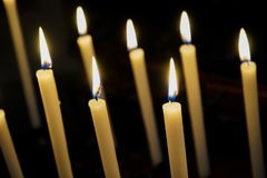 Some lit candles in a church. Votive candles in a church in Murazzano, Piedmont-Italy Royalty Free Stock Images