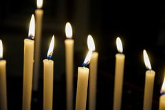 Some lit candles in a church. Votive candles in a church in Murazzano, Piedmont-Italy Stock Photo