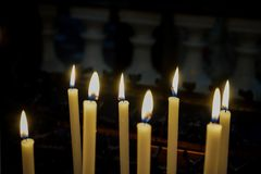 Some lit candles in a church. Votive candles in a church in Murazzano, Piedmont-Italy Stock Photography