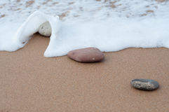 Some little stones in the sand and wave coming, beach shore Royalty Free Stock Photo