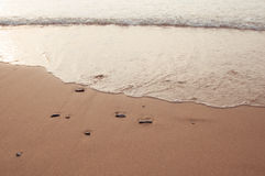Some little stones in the sand and wave coming, beach shore Stock Photography