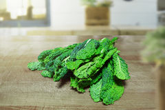 Some loose kale leaves on a wooden table in a rustic kitchen. Empty copy space. For Editor`s content Royalty Free Stock Images