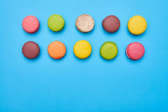Some macaroons arranged in two lines isolated over blue flatlay. Colorful homemade macarons royalty free stock images