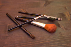 Some Makeup brushes on wood. Some makeup brushes on a wooden table Royalty Free Stock Photography