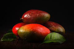 Some mango on wooded board. Black background. Royalty Free Stock Photos