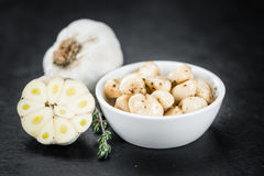 Some Marinated Garlic on a dark slate slab. Portion of Garlic preserved on a rustic slate slab selective focus; close-up shot stock photo