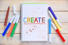 Some markers on a white wooden desktop and a notebook with the word CREATE colorful hand written on it. Stock Images